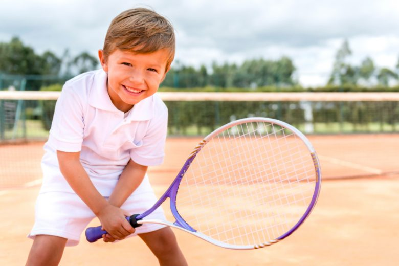 Boy playing tennis and looking very happy